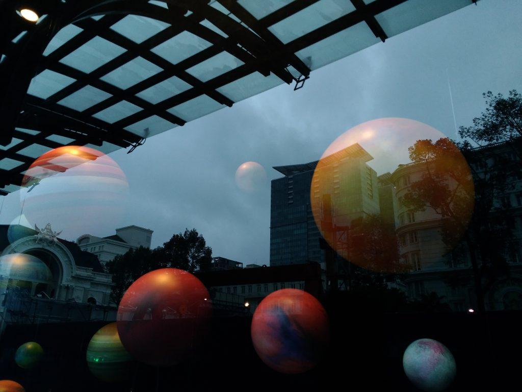 Chụp qua cái gương chỗ trưng bày đồ thời trang, họ trang trí các mô hình các hành tinh nhìn đẹp diệu.